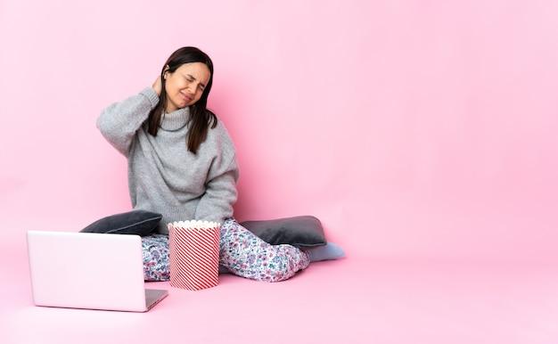 Junge frau, die popcorn isst, während sie einen film auf dem laptop mit nackenschmerzen sieht