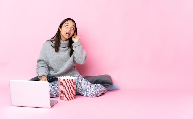 Junge frau, die popcorn isst, während sie einen film auf dem laptop sieht, der etwas hört, indem man hand auf das ohr legt