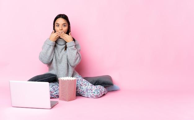 Junge frau, die popcorn isst, während sie einen film auf dem laptop sieht, der mund mit händen kegelt