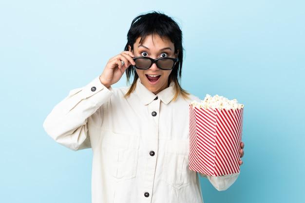 Junge frau, die popcorns über isolierter wand isst