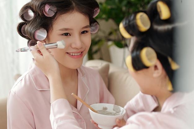 Junge frau, die porenverfeinernde tonmaske auf das gesicht ihres lächelnden freundes spa-tag zu hause konzept aufträgt