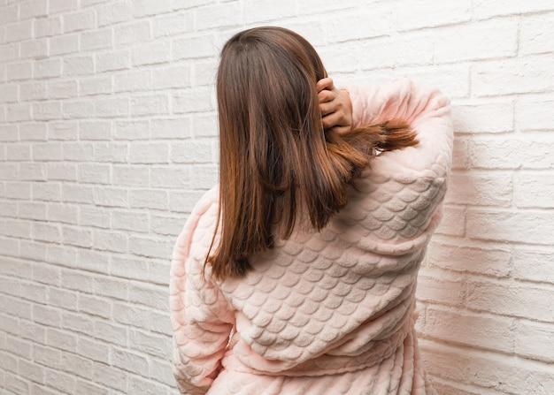 Junge frau, die pyjama von hinten trägt, über etwas denkend
