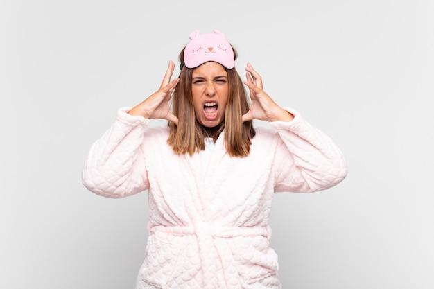 Junge frau, die pyjamas trägt, mit den händen in der luft schreit, sich wütend, frustriert, gestresst und verärgert fühlt