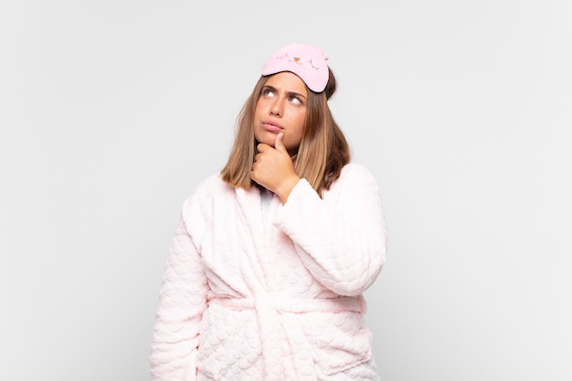 Junge frau, die pyjamas trägt, nachdenkt, sich zweifelnd und verwirrt fühlt, mit verschiedenen optionen und sich fragt, welche entscheidung sie treffen soll