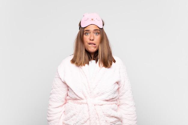 Junge frau, die pyjamas trägt, verwirrt und verwirrt aussieht, mit einer nervösen geste auf die lippe beißt und die antwort auf das problem nicht kennt