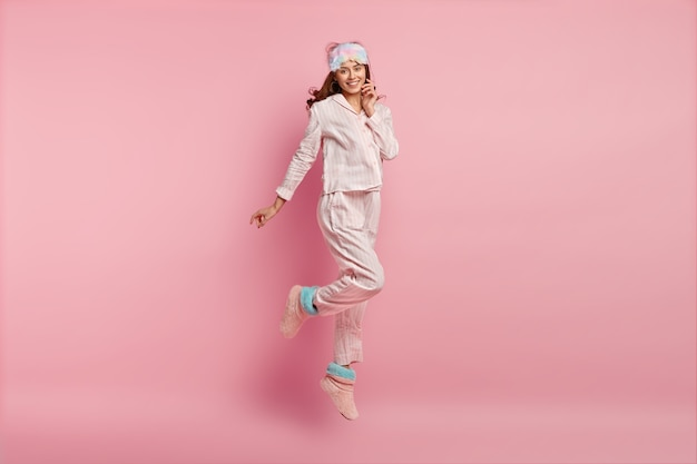 Junge frau, die pyjamas und schlafmaske trägt