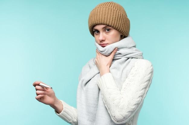 Junge frau, die rauchgasthermometer gegen blauen raum nimmt. schöne dame ist krank mit einer hohen temperatur und halsschmerzen, isolierte nahaufnahme. erkältung, grippe-konzept.