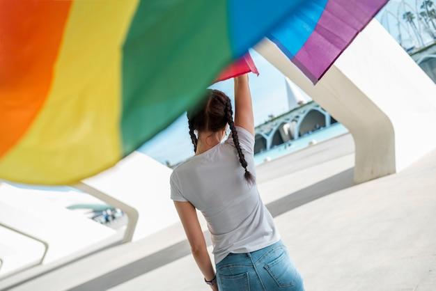 Junge frau, die regenbogenflagge hält