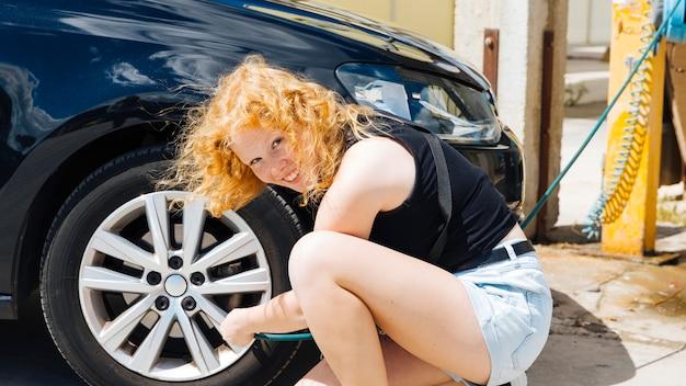 Junge frau, die reifen des autos an der tankstelle am sonnigen sommertag aufpumpt
