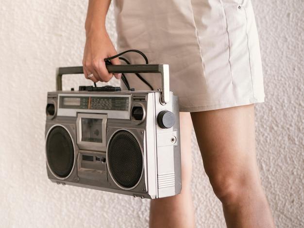 Junge frau, die retro- musikspieler hält