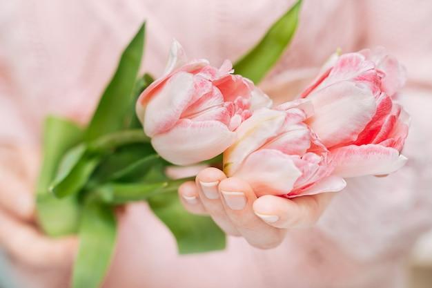 Junge frau, die rosa tulpen auf einem weißen hintergrund hält. unscharfes porträt, nahaufnahme, kopierraum, selektiver fokus.