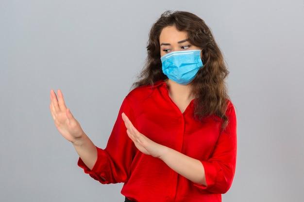 Junge frau, die rote bluse in der medizinischen schutzmaske trägt, die hände hält, die erzählen, kommen nicht näher über isolierten weißen hintergrund