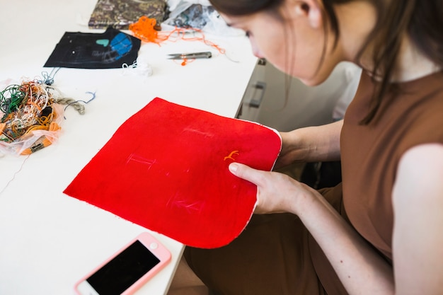 Junge frau, die roten stoff mit smartphone auf schreibtisch näht