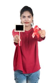 Junge frau, die rotes band hiv, aids-bewusstseinsband und kleine tafel, gesundheits- und medizinkonzept zeigt