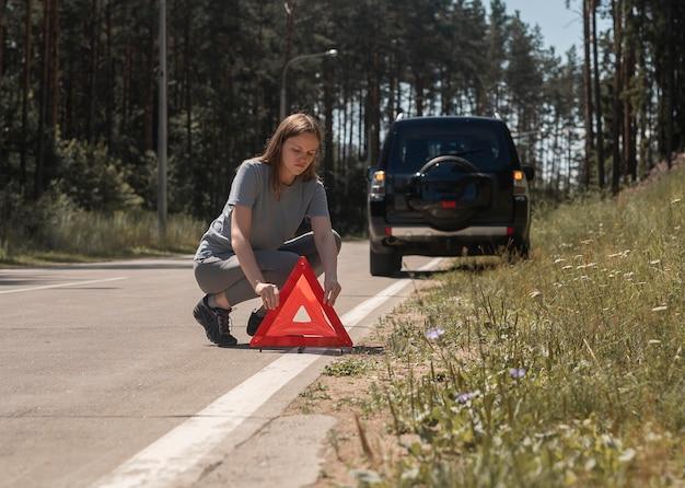 Junge frau, die rotes dreieck-warnschild auf straße in der nähe von kaputtem auto am straßenrand setzt