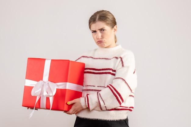 Junge frau, die rotes geschenk auf weiß hält