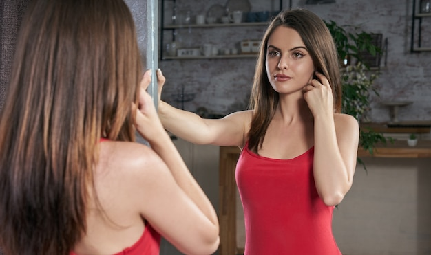Junge frau, die rotes kleid trägt und sich selbst im spiegel betrachtet