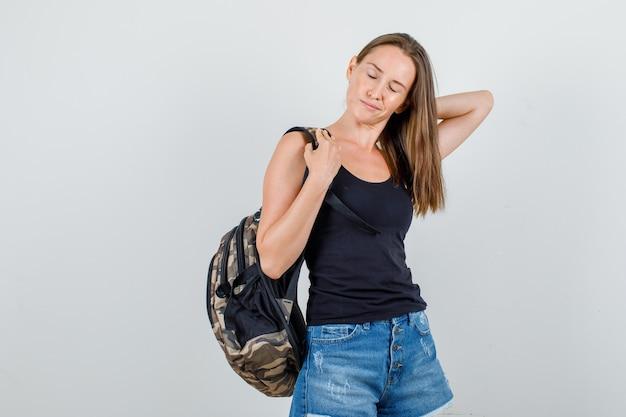 Junge frau, die rucksack mit geschlossenen augen im unterhemd, shorts hält