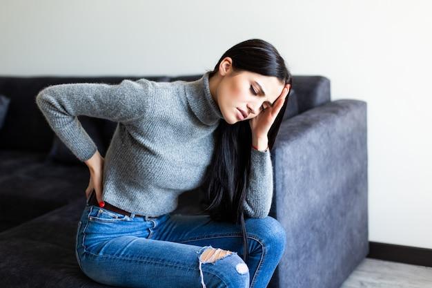 Junge frau, die rückenschmerzen leidet und sich beschwert, auf einer couch im wohnzimmer zu hause zu sitzen