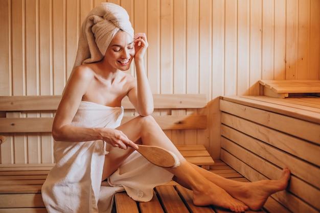Junge frau, die ruhe in der sauna allein hat