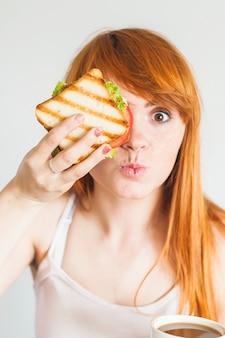 Junge frau, die sandwich vor ihren augen hält