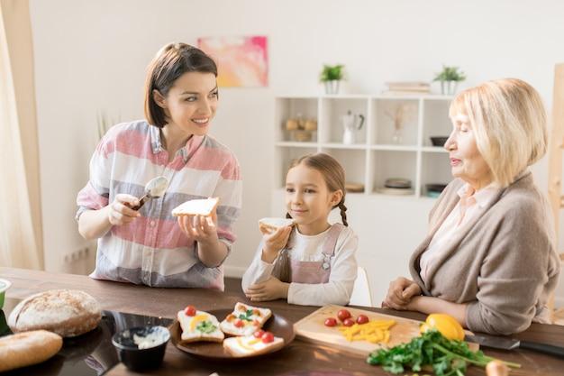 Junge frau, die sandwiches zum frühstück macht und mit ihrer mutter in der küche mit der kleinen tochter spricht, die in der nähe isst