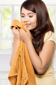 Junge frau, die saubere frische wäsche riecht