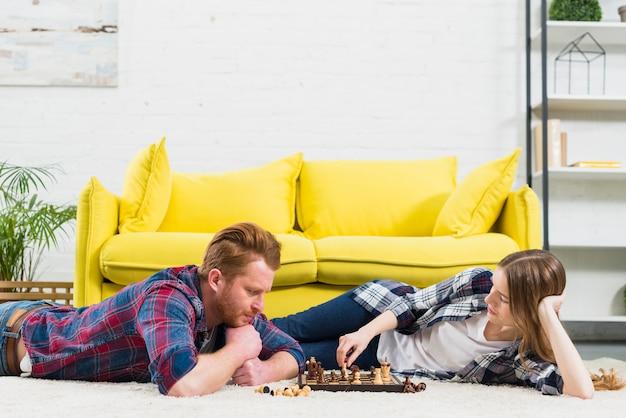 Junge frau, die schachspiel mit ihrem freund spielt