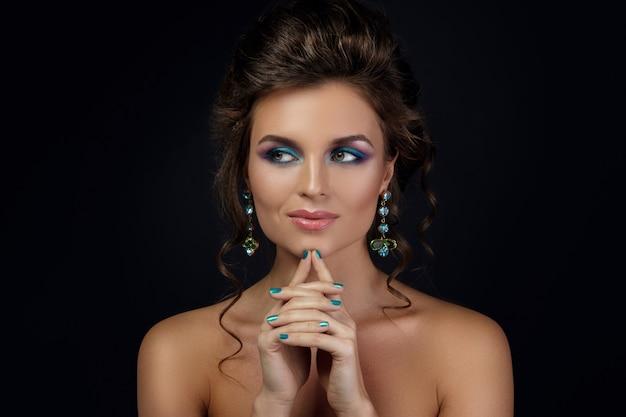 Junge frau, die schöne ohrringe mit edelsteinen trägt Premium Fotos