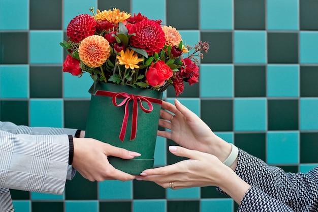 Junge frau, die schöne pfingstrosenblumen von der lieferfrau erhält.