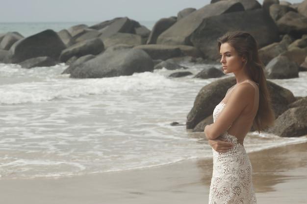 Junge frau, die schönes weißes kleid trägt, posiert am felsigen strand