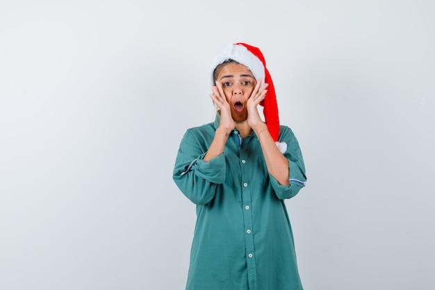 Junge frau, die schreit, indem sie die hände in der nähe des mundes im hemd, in der weihnachtsmütze hält und beunruhigt aussieht, vorderansicht.