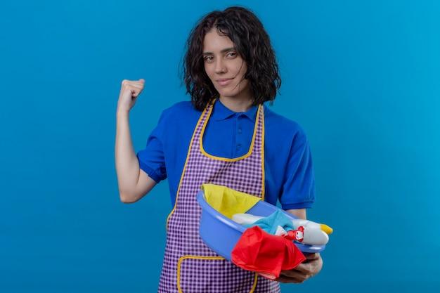 Junge frau, die schürze hält becken mit reinigungswerkzeugen, die faust anheben zeigt bizeps lächelnd zuversichtlich bereit zu reinigen steht über isoliertem blauem hintergrund