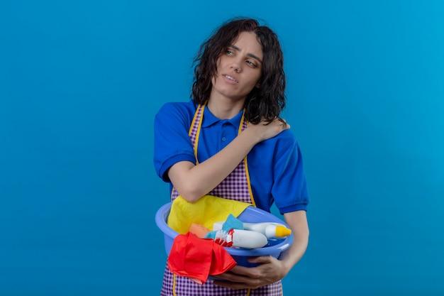 Junge frau, die schürze hält becken mit reinigungswerkzeugen trägt, die überarbeitete berührende schulter suchen, die schmerzen über blauer wand hat