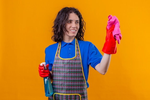 Junge frau, die schürze und gummihandschuhe trägt, die reinigungsspray und teppich lächelnd mit glücklichem gesicht bereit yo sauberes stehen über lokalisiertem orangefarbenem hintergrund halten