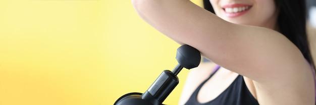 Junge frau, die schultermuskelmassage mit schlagmassagegerätnahaufnahme tut