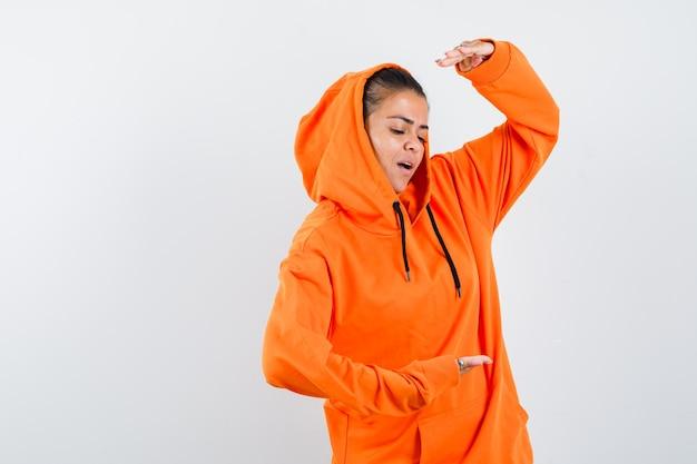 Junge frau, die schuppen in orangefarbenem hoodie zeigt und fokussiert aussieht