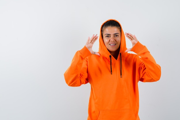 Junge frau, die schuppen in orangefarbenem hoodie zeigt und schön aussieht