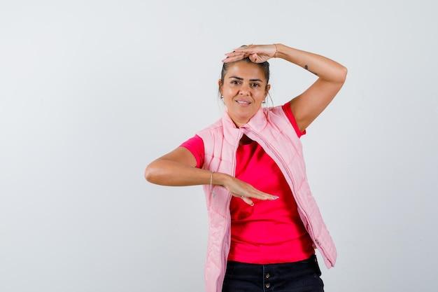 Junge frau, die schuppen in rosa t-shirt und jacke zeigt und glücklich aussieht
