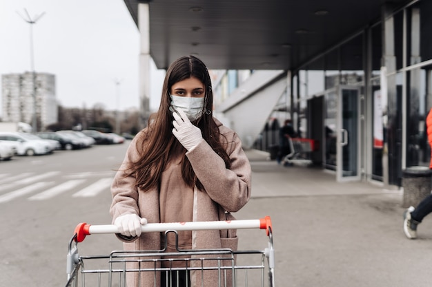 Junge frau, die schutzgesichtsmaske gegen coronavirus 2019-ncov trägt, der einen einkaufswagen schiebt. konzept des coronavirus