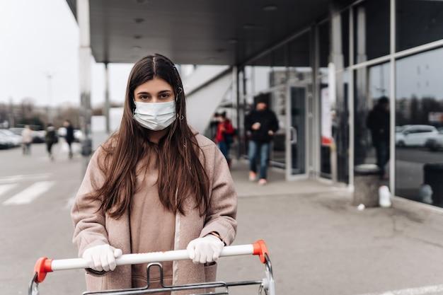 Junge frau, die schutzgesichtsmaske gegen coronavirus 2019-ncov trägt, der einen einkaufswagen schiebt.