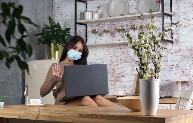 Junge frau, die schutzgesichtsmaske mit laptop für videoanruf zu hause trägt