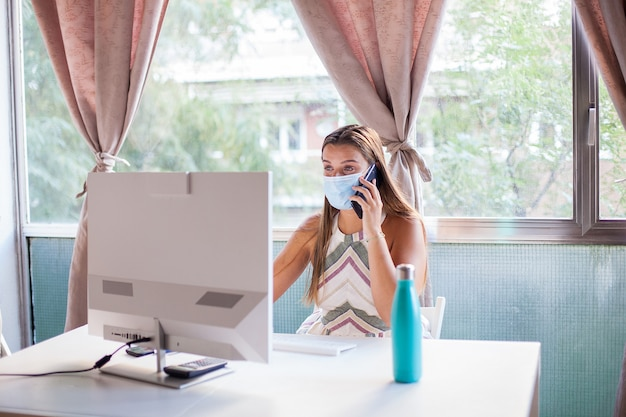 Junge frau, die schutzmaske trägt, die vom hauptbüro wegen des ausbruchs des coronavirus arbeitet