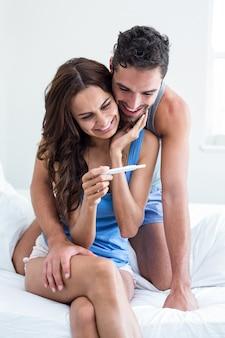 Junge frau, die schwangerschaftstest während ehemann umfasst auf bett hält