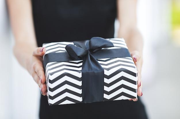 Junge frau, die schwarze freitagsgeschenke hält. geschenkbox