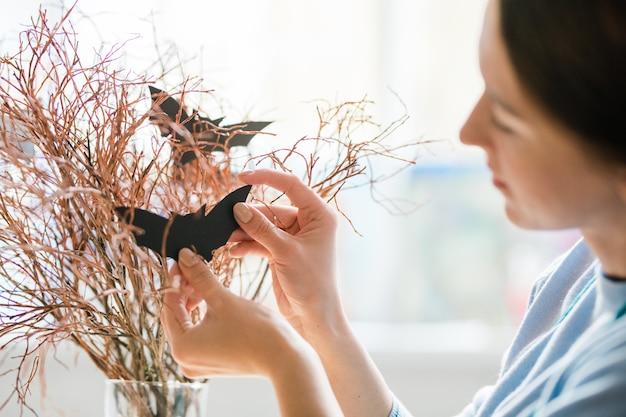 Junge frau, die schwarze handgemachte fledermäuse auf trockenen zweigen hängt, während dekorationen für halloween vorbereiten