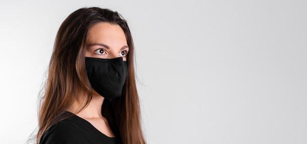 Junge frau, die schwarze schutzmaske trägt. grippe oder viruspandemie. allergiesaison