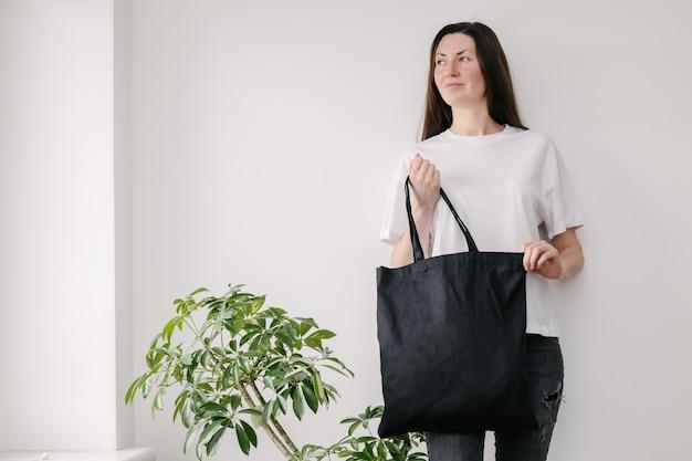 Junge frau, die schwarze textil-öko-tasche gegen weiße wand hält.