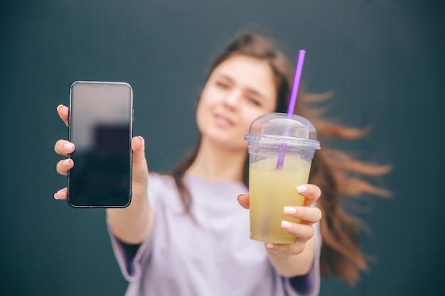 Junge frau, die schwarzes smartphone und tasse limonade in händen hält und es zeigt