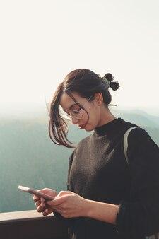 Junge frau, die sein telefon in einem berg während eines sonnigen tages überprüft